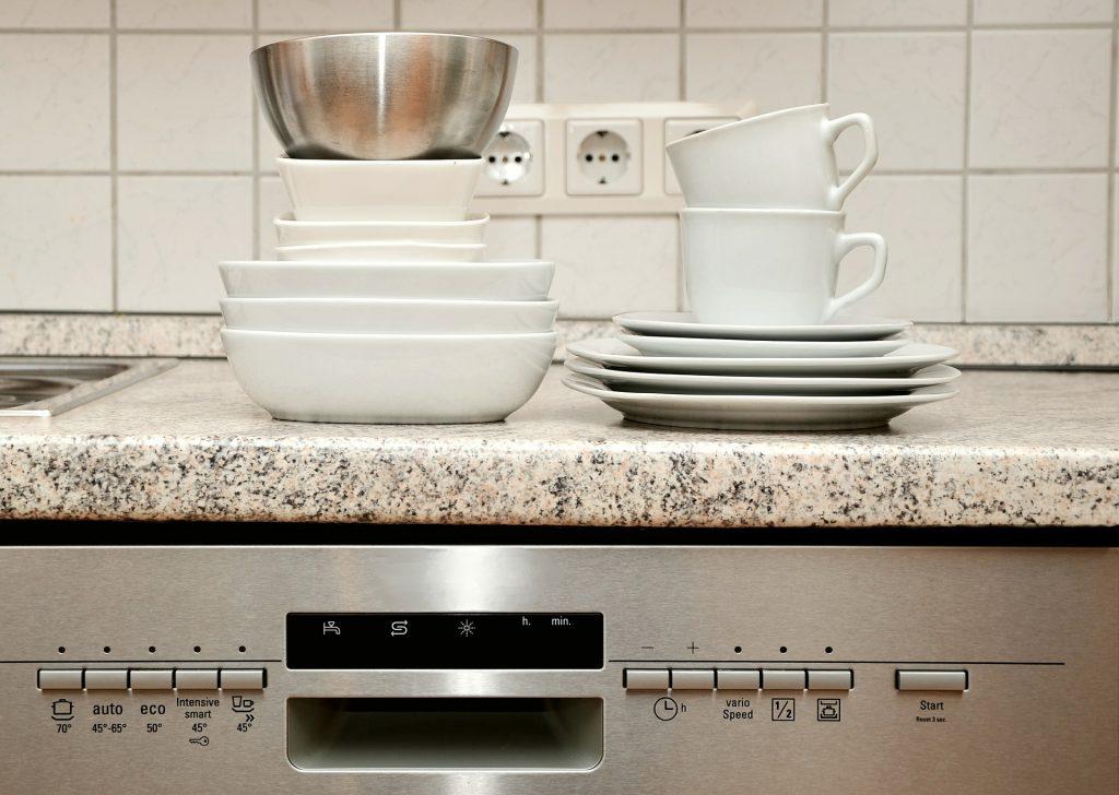 Auf einer Spülmaschine sind Teller und Tassen gestapelt.