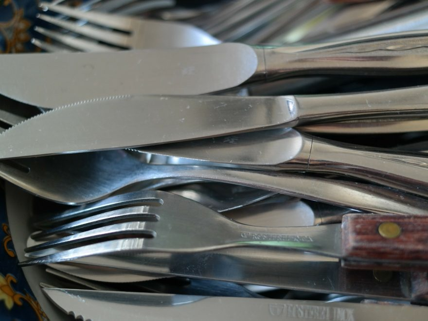 Gabel und Messer unsortiert auf einem Stapel.