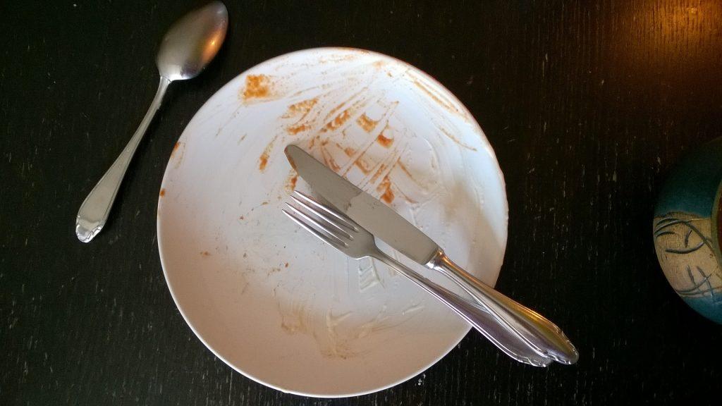 Ein leerer Teller mit Essensreste und Besteck